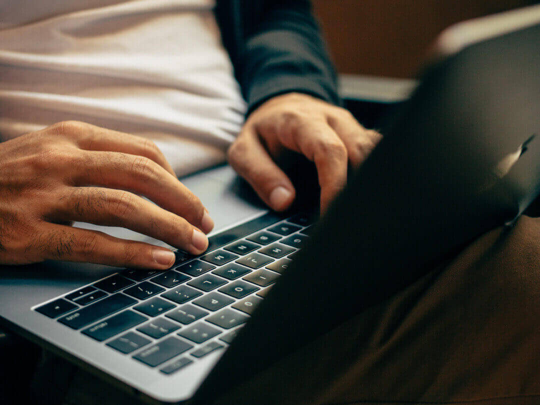 Photo of a user typing on laptop