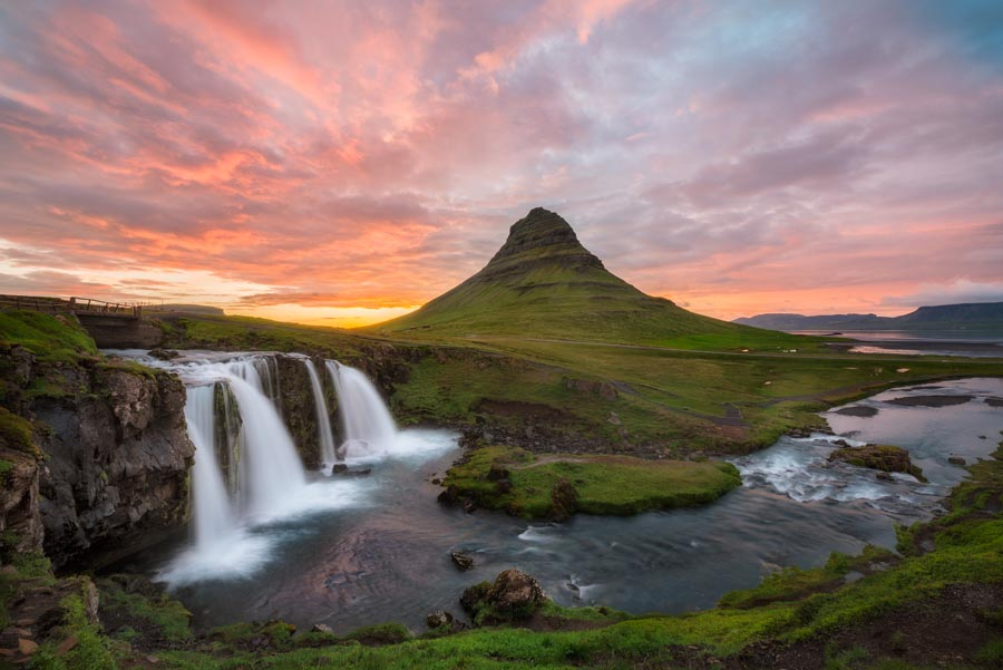 Midnight sun lights up the sky behind Kirkjufell mountain in Grundarfjörður, Iceland