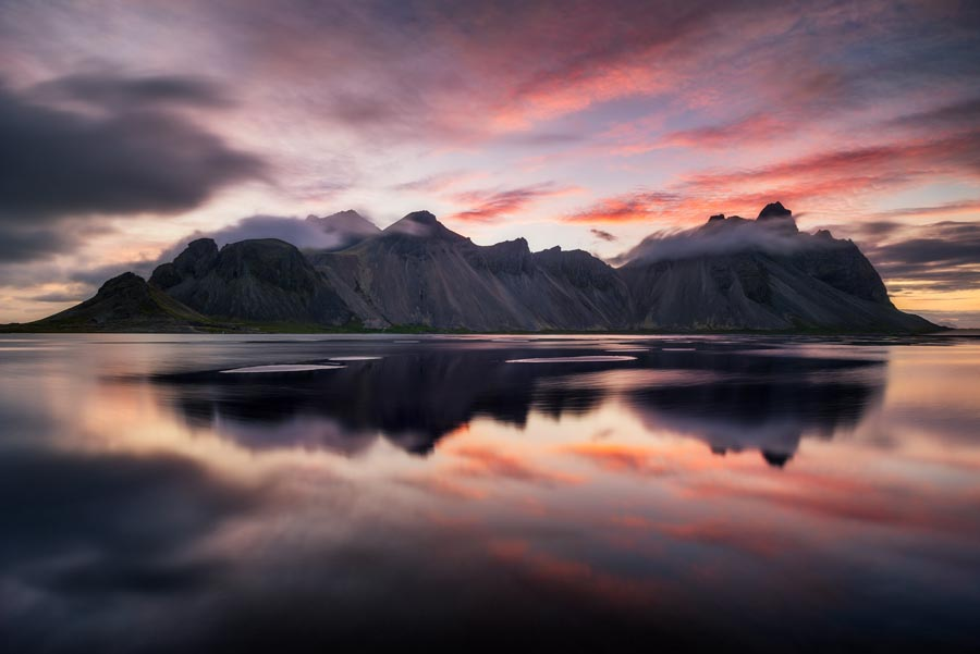 Jagged peaks of Vestrahorn mountain reflect in the North Atlantic sea in Iceland