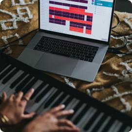 joue du piano sur son lit avec un écran d'ordinateur hello virtuoso