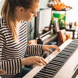 jeune fille blonde qui joue sur un piano numérique
