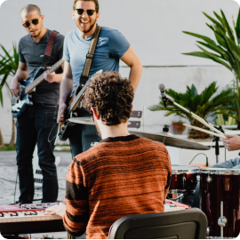 trois musiciens riant et jouant du piano et de la guitare ensemble