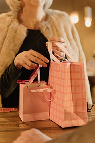 Starija gospođa u rukama drži ukrasne roze kese.