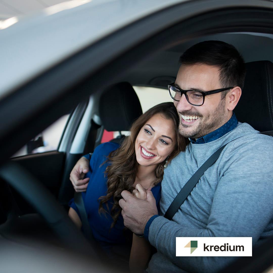 Momak sa naočarima i devojka  nasmejani i zagrljeni sede u automobilu držeći se za ruke.
