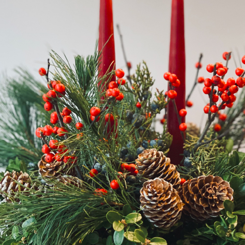 Accents of red winterberry, pine cones and fresh holiday greens of boxwood and pine with two tapered candles set in a silver vase make this the perfect centerpiece to enjoy the season. A warm and heartfelt way to say Merry Christmas to friends or family near and far.