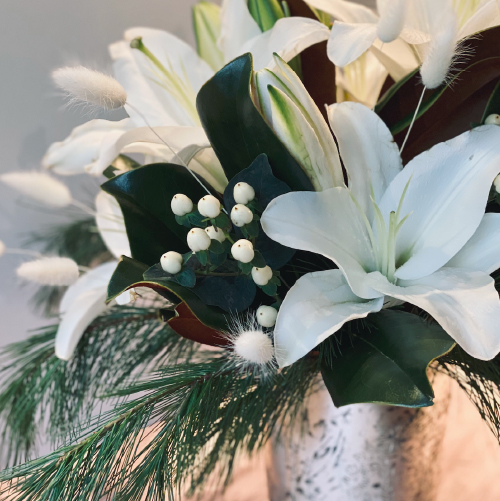 Fresh winter magnolia leaves accompanied with white lilies and fuzzy soft bunny tail, accented with seasonal greens all set in a silver leaf type vase.