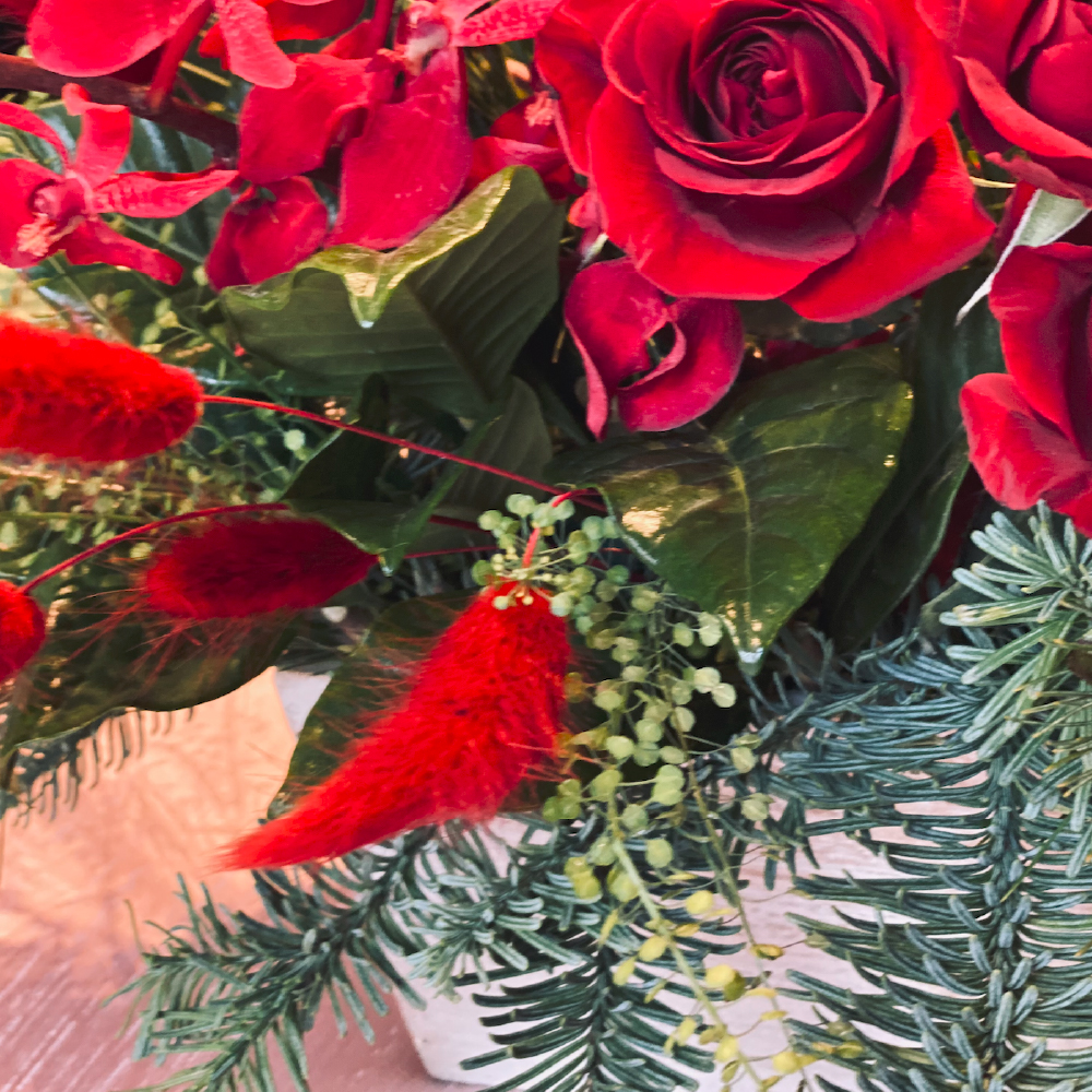 More than a dozen small red roses and red orchids accented with soft plushy red bunny tail and finished with the most perfect seasonal greens.