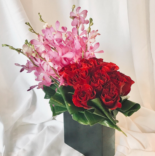 A passionate display of Dark Velvety Red Roses & Pink Mokara Orchids in a black vase.