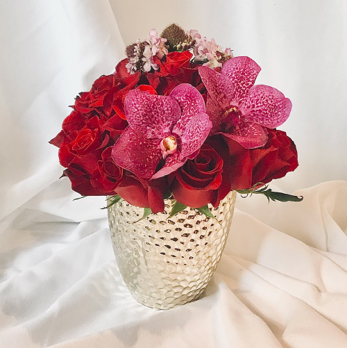 This lovely compact arrangement has red Roses from France packed tightly with an accent of pink Vanda Orchid blooms from Thailand