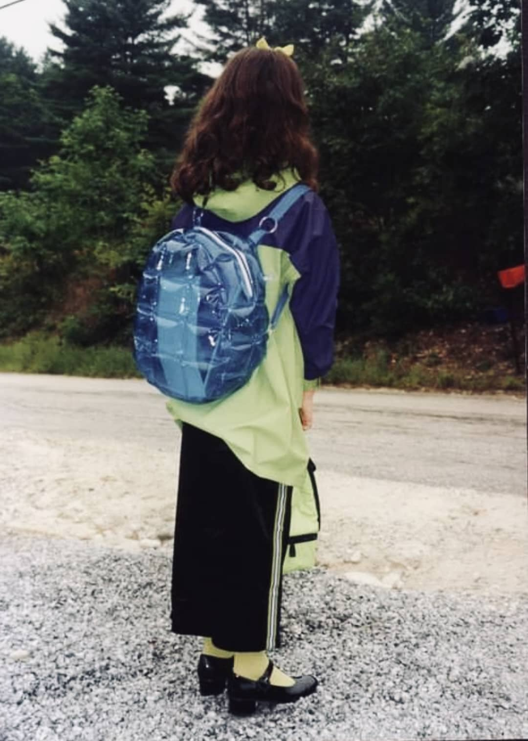A young girl standing with her back to the camera. She's wearing a long dress, tights, heels, rain jacket, and is wearing an inflatable backpack.