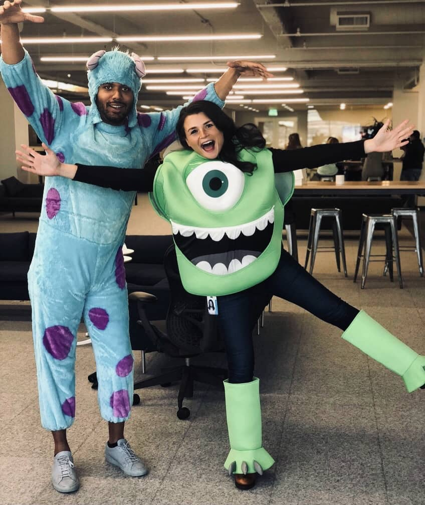 A man wearing a Sully costume and a woman wearing a Mike Wasowski costume from Monsters Inc. posing silly.