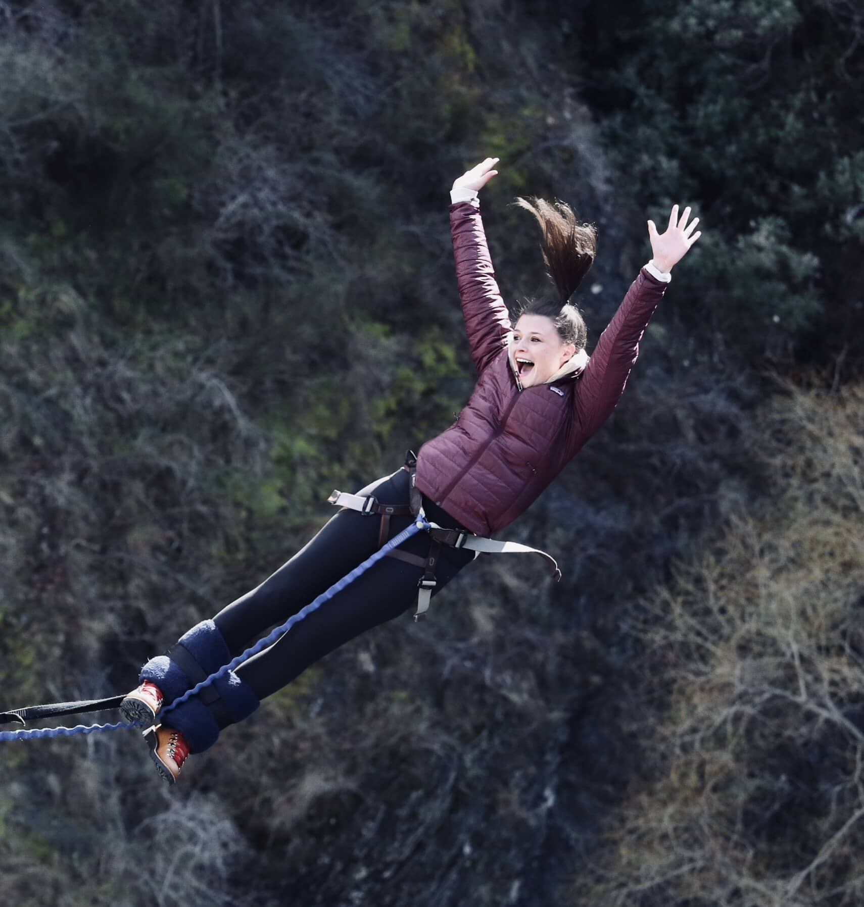 A woman bunny jumping with her arms stretching above her and a big smile on her face.