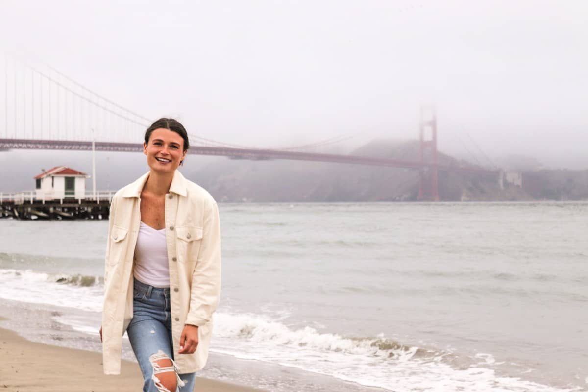 Woman smiling and walking on beach towards the camera; the Golden Gate Bridge is in the background with a layer of fog kissing the top of the bridge