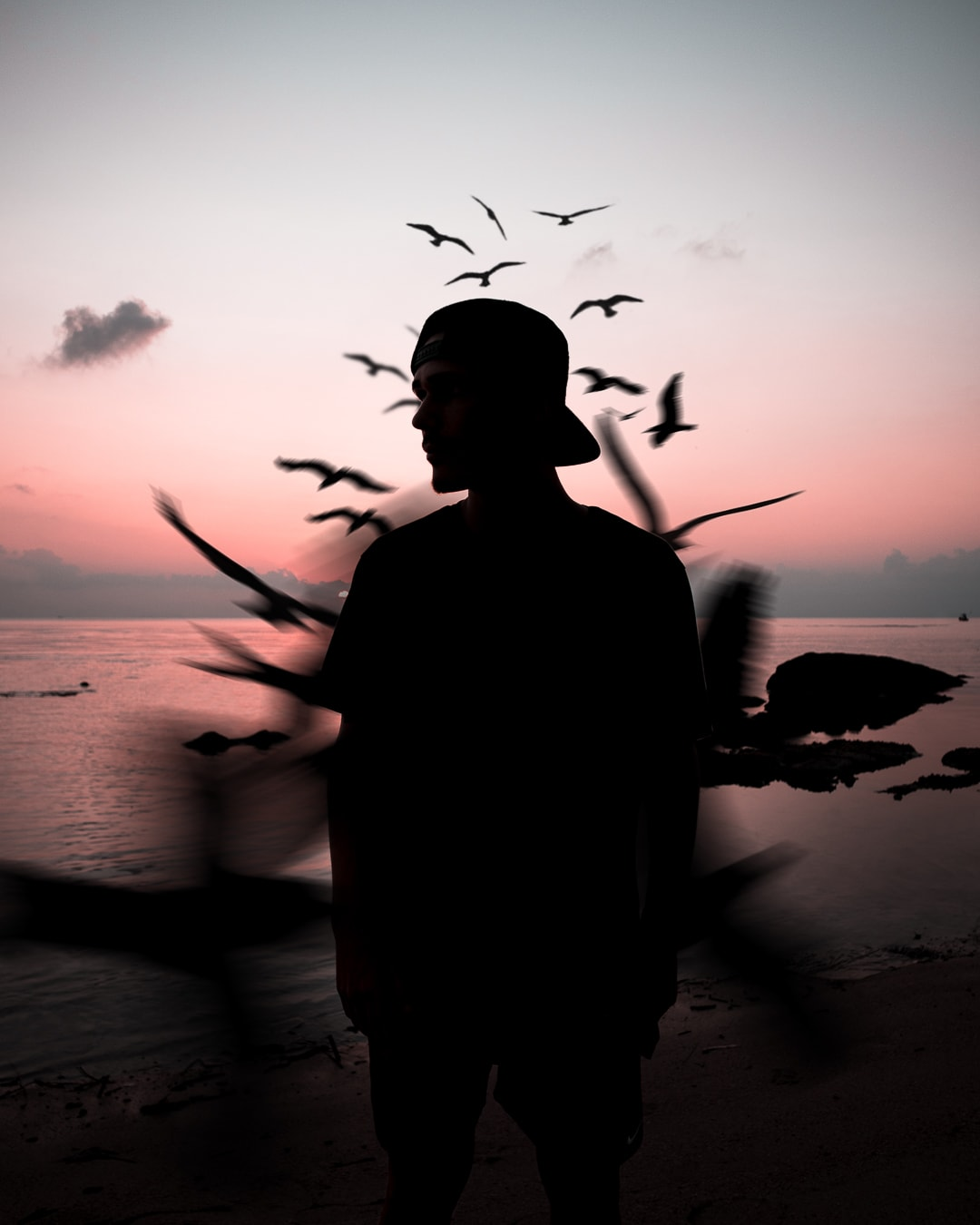 Portrait and composition of Athos Abreu on the beach at sunset. Birds fly in circles around him.