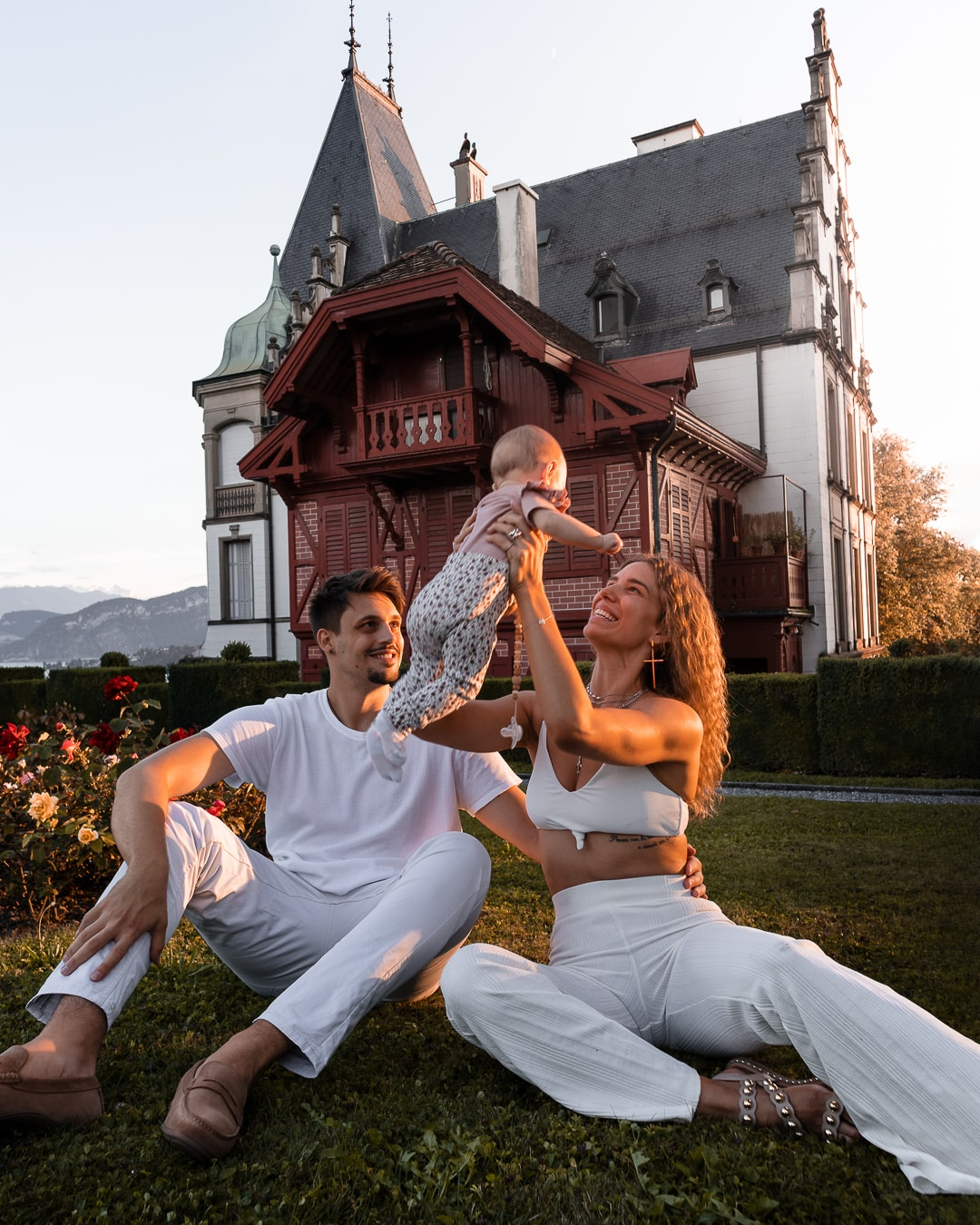 Family picture of Anja Zeidler, Milan Anicic and her child. They are sitting in front of the famous Meggenhorn Castle and Anja holds her child in the air.