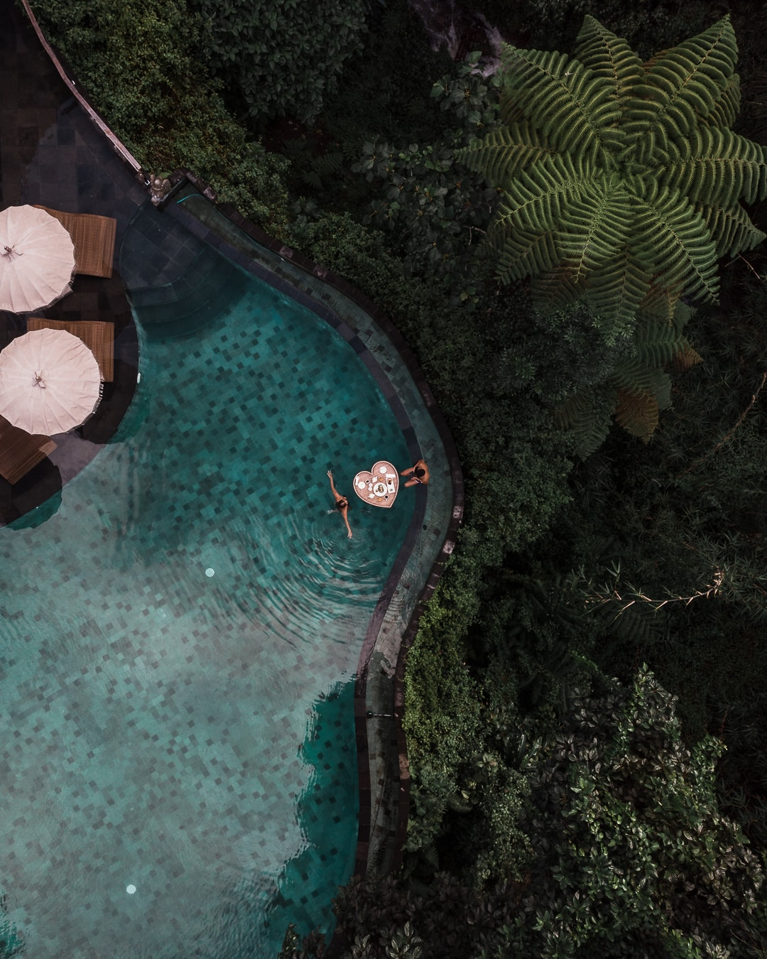 Drone image of Travelermentality having breakfast in the pool water of the Aksari Resort in Bali, Indonesia.