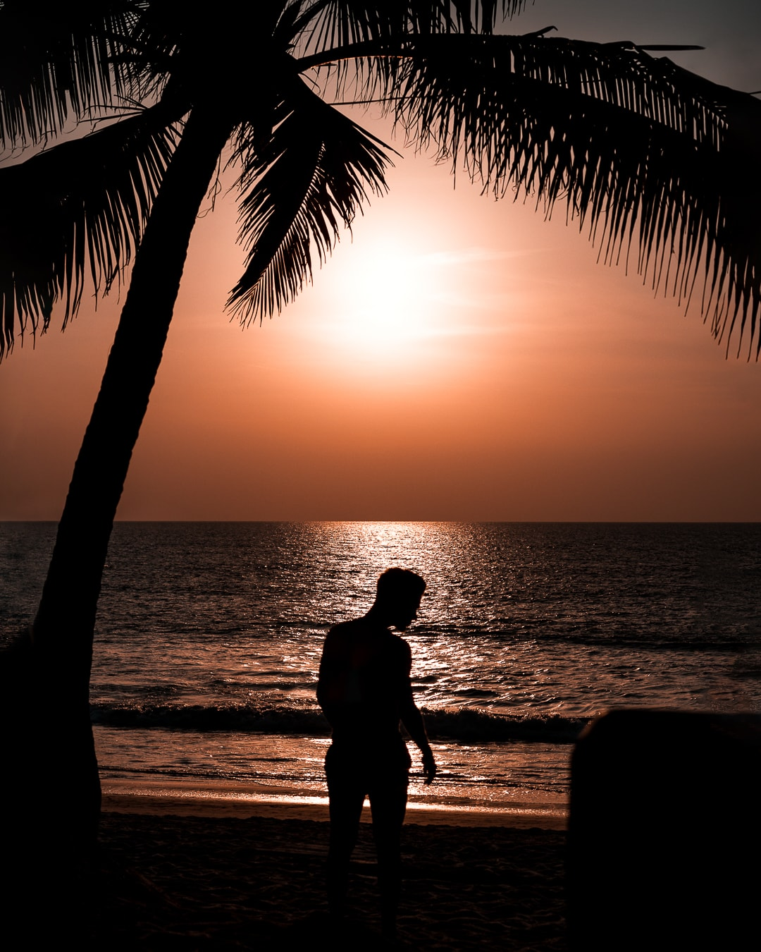 Portrait of Athos Abreu on the beach at sunset. You can only see the silhouettes.