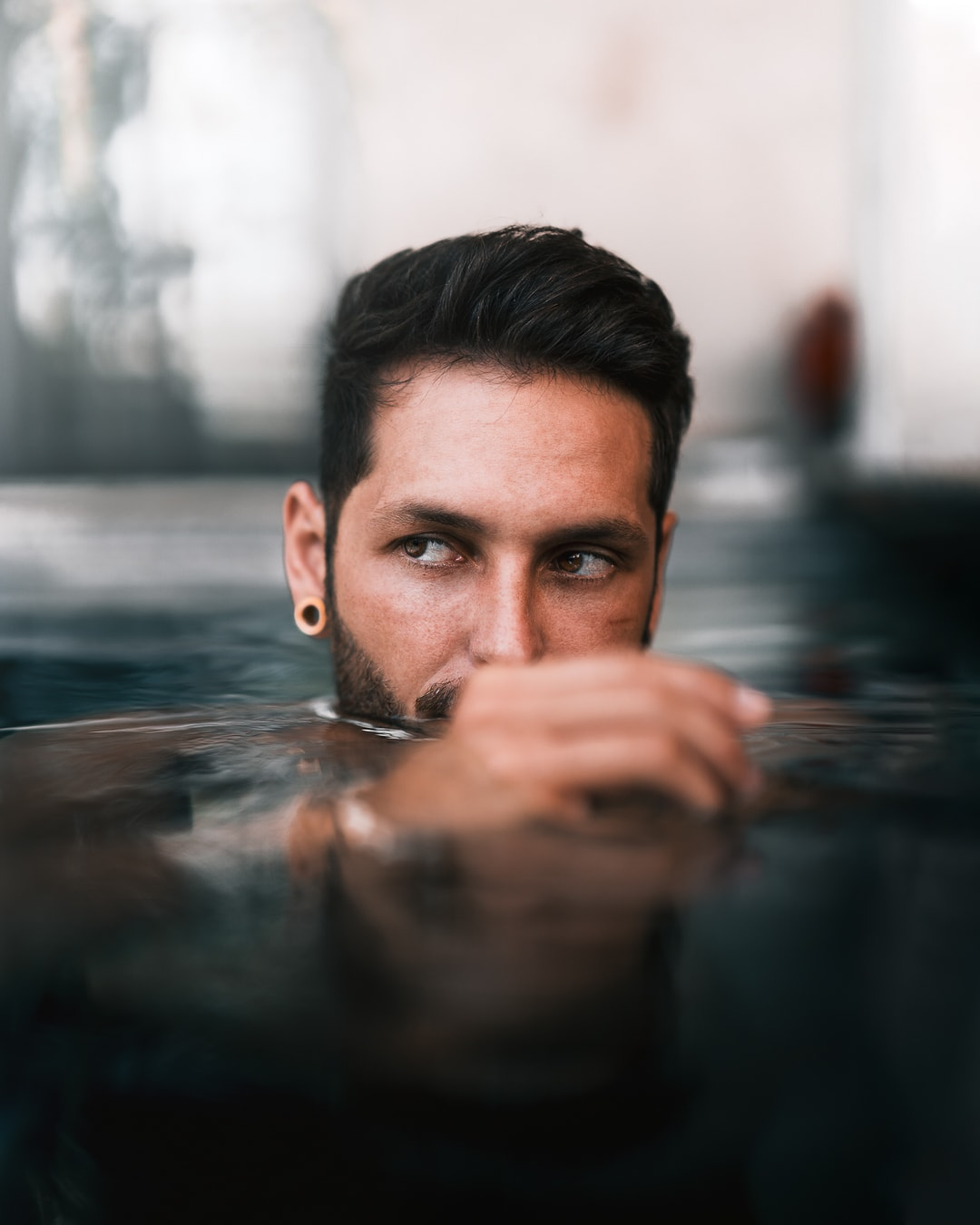 Portrait of the influencer Giulio Gröbert in the water. He holds his hand in front of his face.