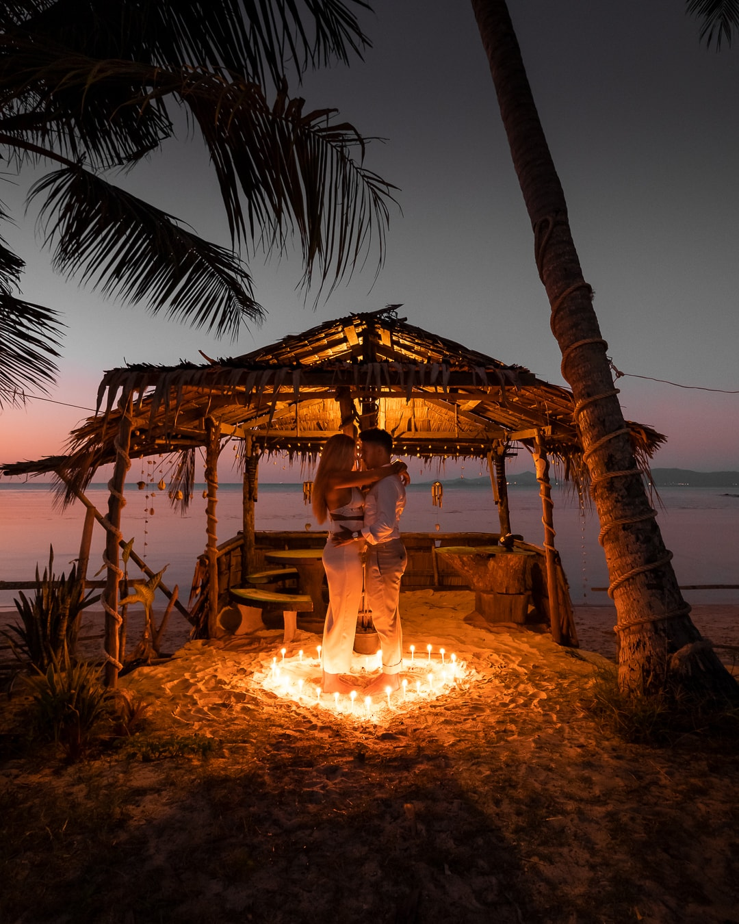 Travelermentality at sunset in front of a beach in Koh Samui, Thailand. They stand and hug each other. Around them candles are spread out in a heart shape. You can see the starry sky.