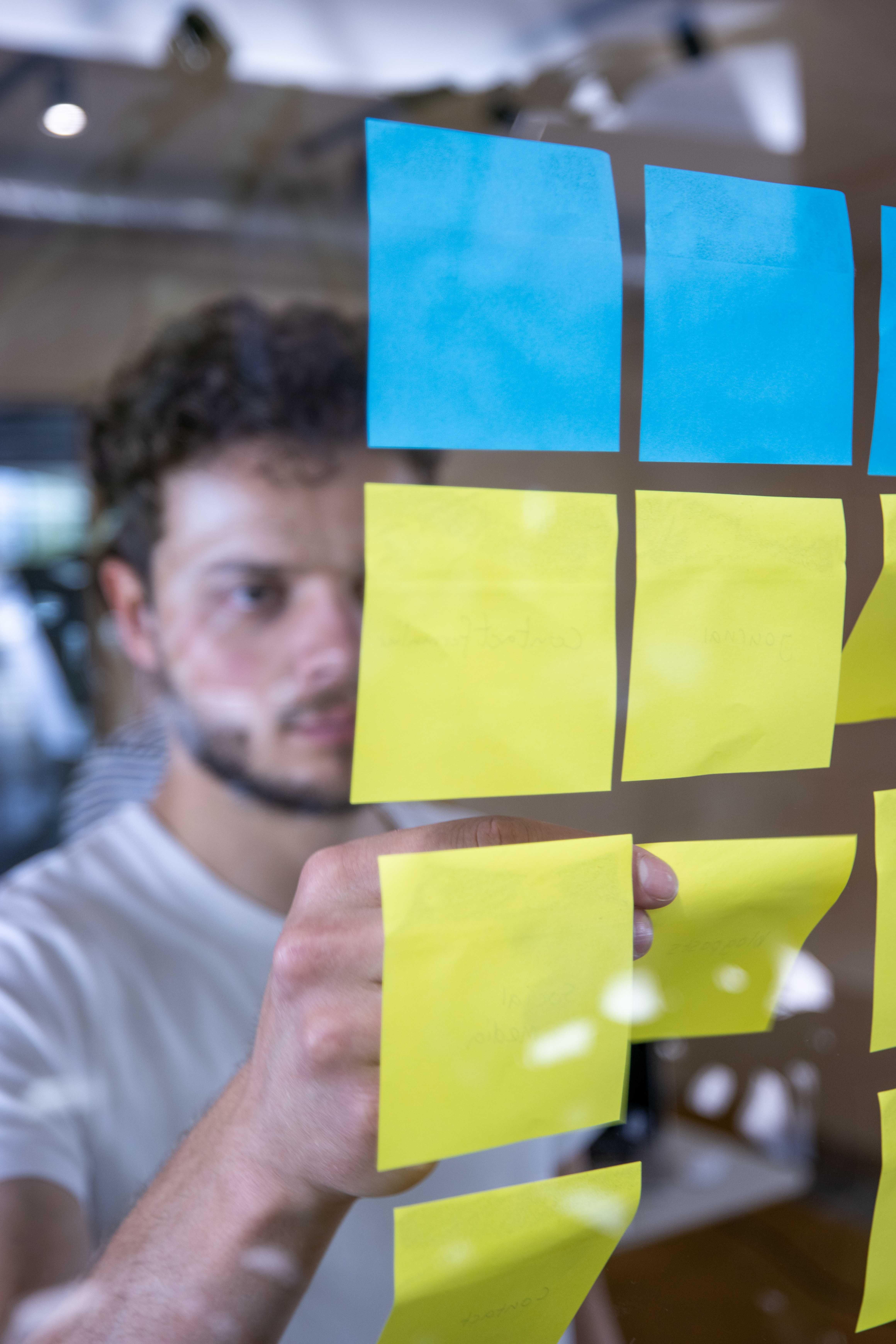 Bas van De Vormbrouwers post-it aan het plakken tijdens een creatieve sessie