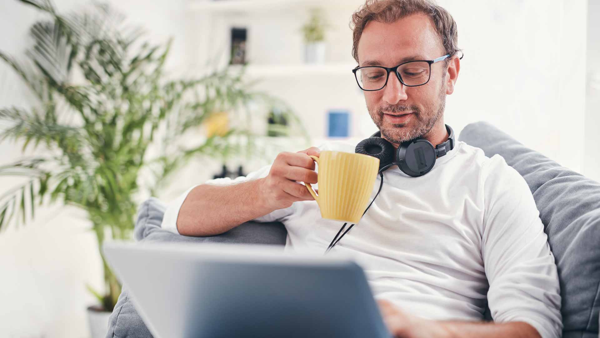 Man sits on a couch with headphones around his necking, sipping coffee while reading.