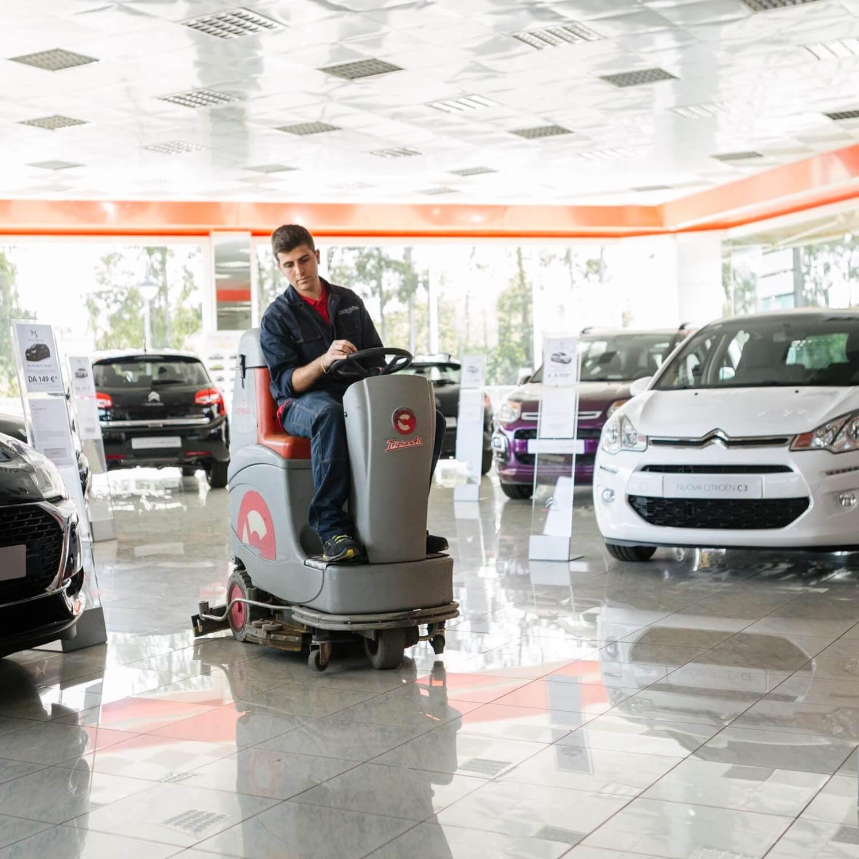 Un uomo su una macchina lavapavimenti in un concessionario auto