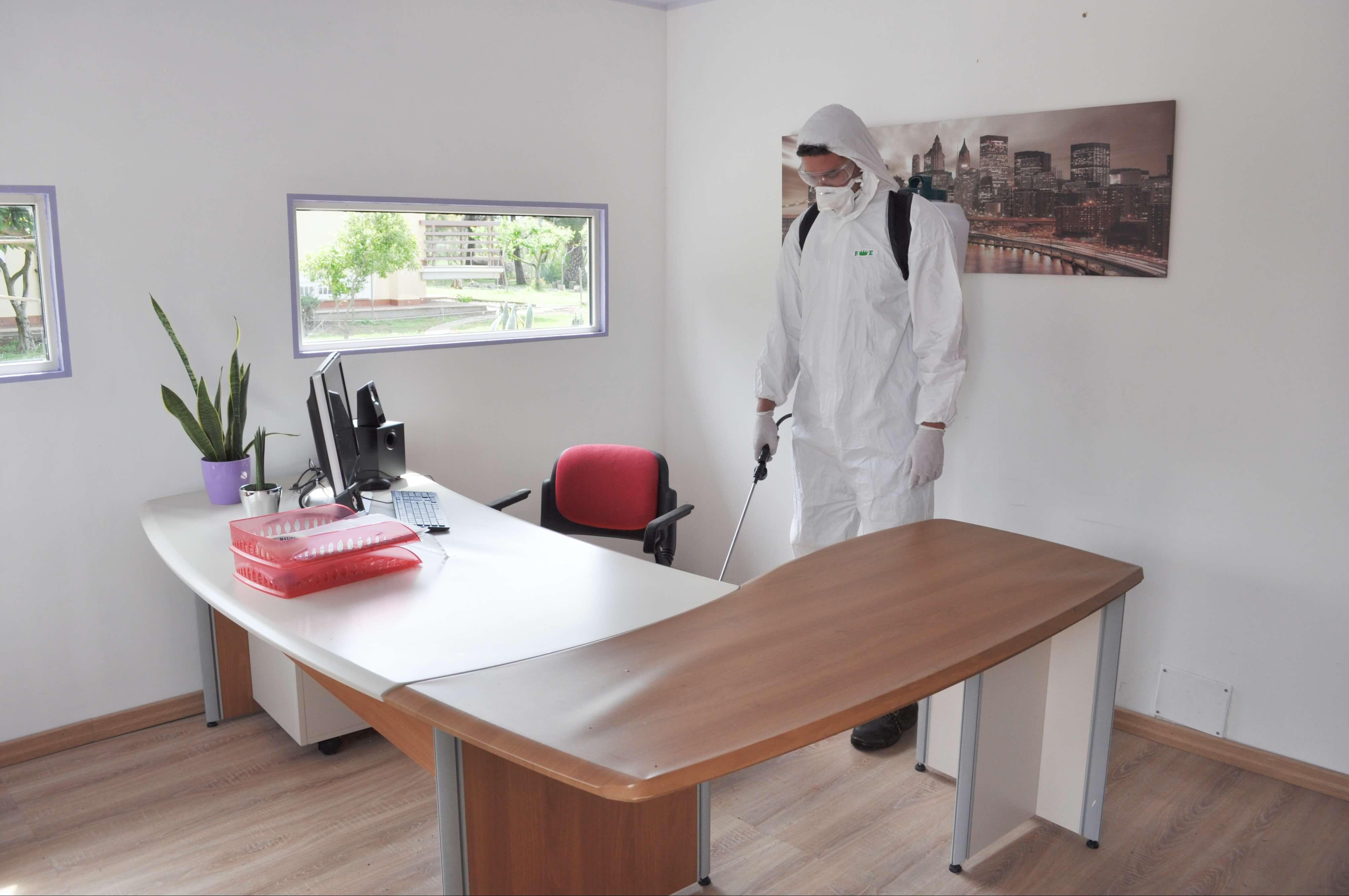 Un operatore munito di dispositivi di protezione personale sta eseguendo una sanificazione covid 19 per aziende a latina in un ufficio