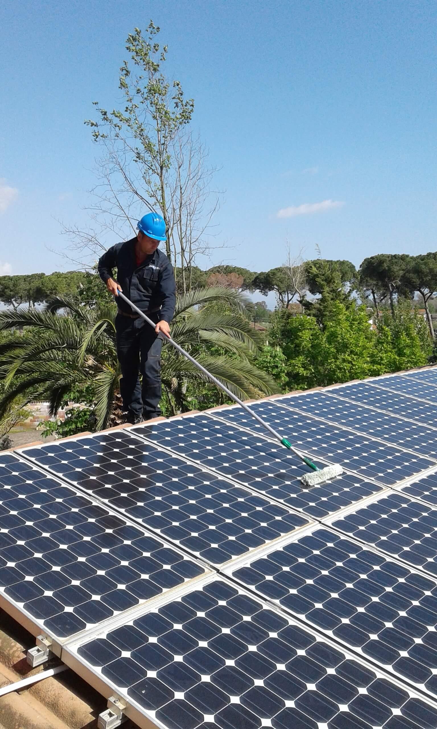 Un uomo su un tetto pulisce dei pannelli solari