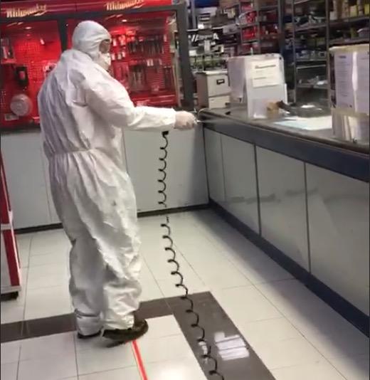 Un operatore con tuta,  mascherina e occhiali protettivi nebulizza il disinfettante in un negozio