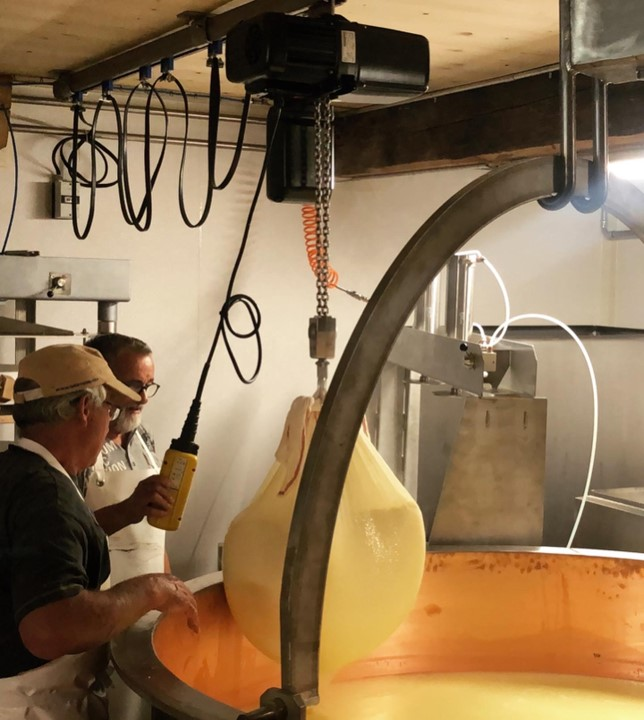 Käse wird aus dem Kessi geholt