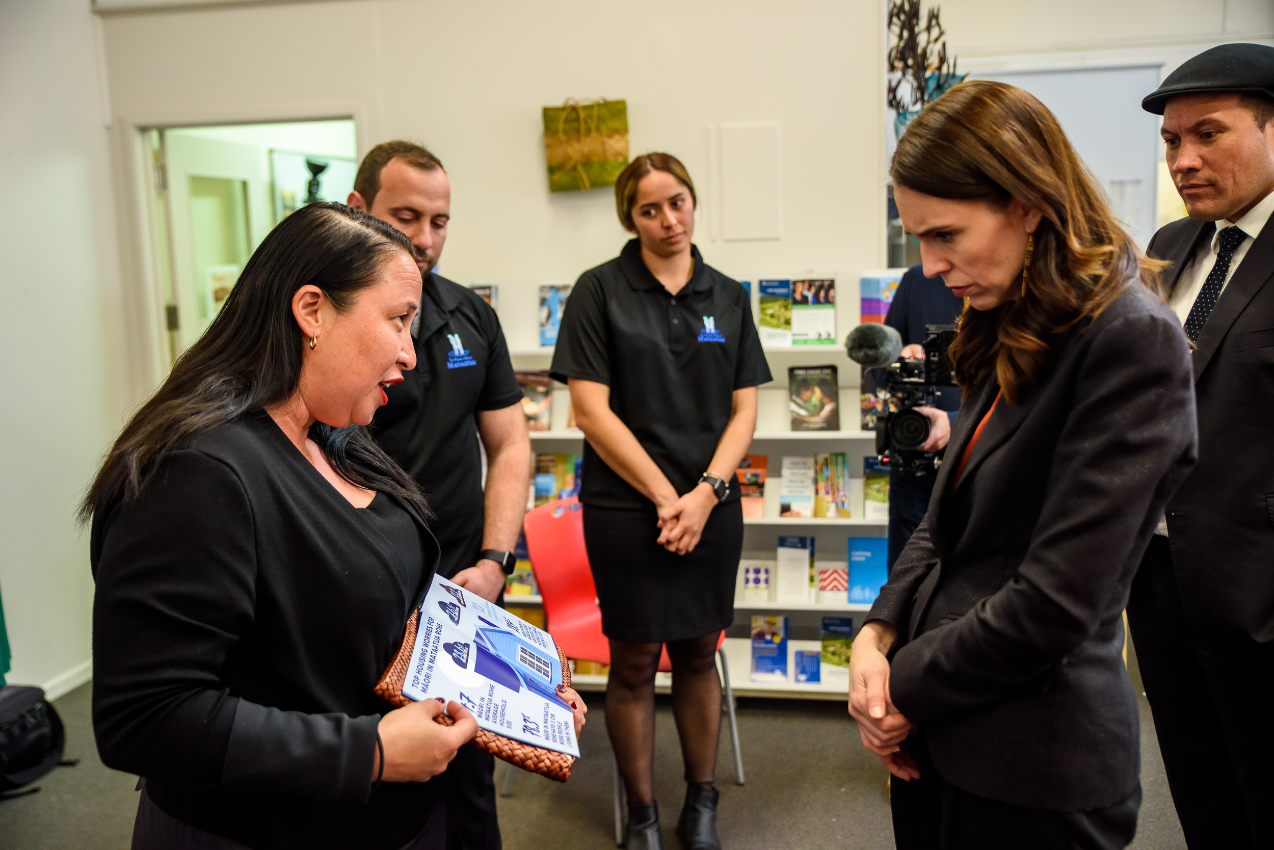 Prime Minister Jacinda Ardern closely examines a poster