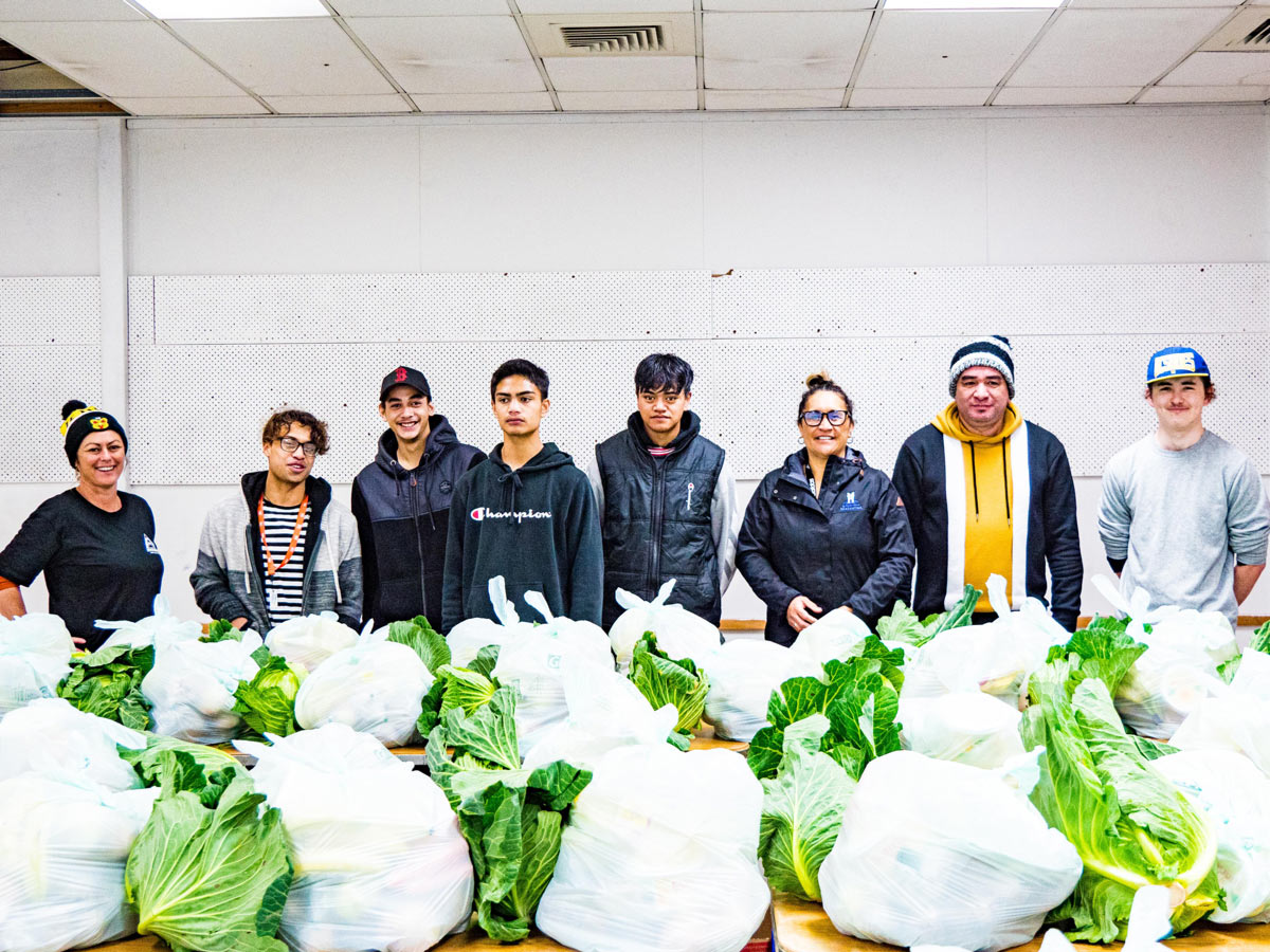 A group of youth stand behind food parcels they have prepared for those in need