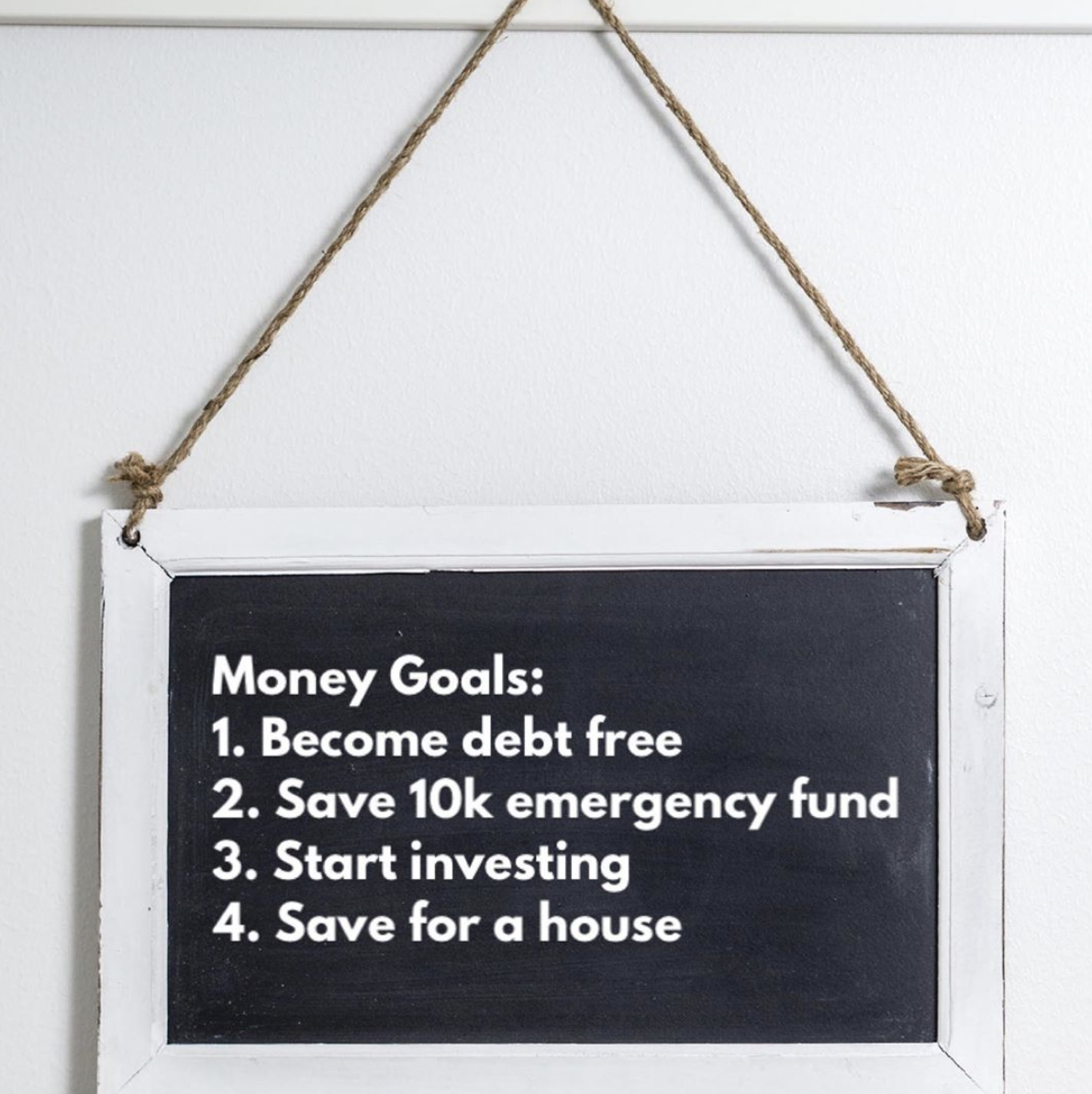 A chalkboard hung on a wall with money goals like become debt free, saving for an emergency fund, saving for a house written on it.