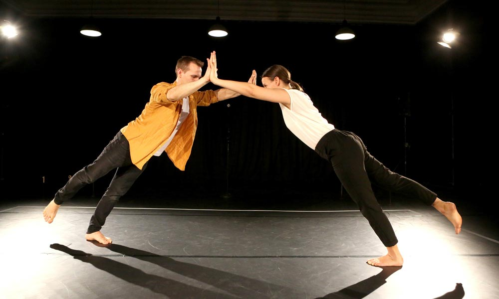 Anna Kempin and Johannes Blattner are dancing at Jukebox 2.0 contemporary dance performance, holding hands and pushing their bodies against each other