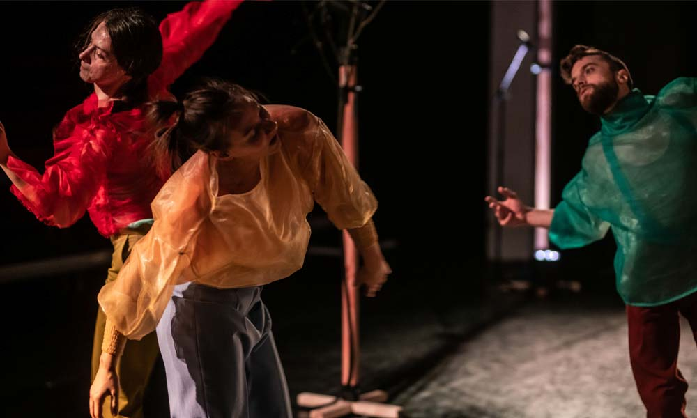 Three modern dancers captured in movement, during Vox contemporary dance performance
