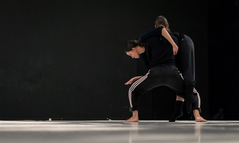 Anna Kempin and other dancer are making complex modern dance moves during a rehearsal