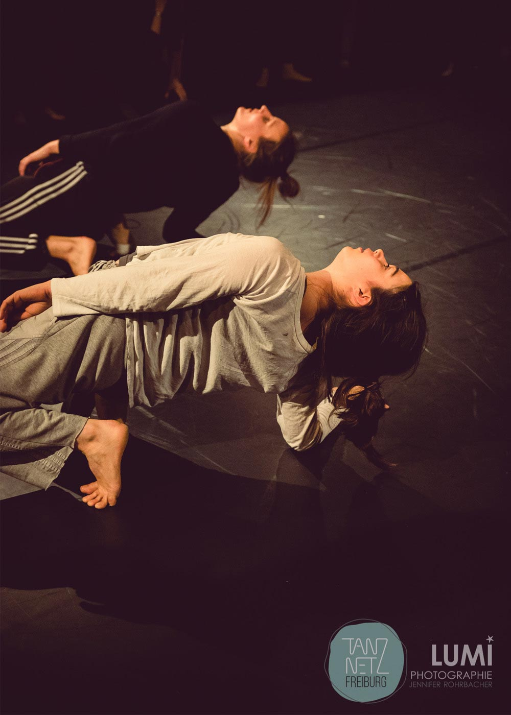 Anna Kempin and other dancer are balancing on their feet with head raised high, touching floor with one hand