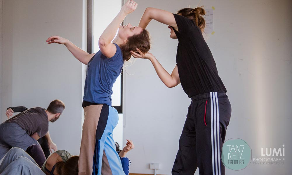 Anna kempin captured during her Tanznetz Freiburg dance workshop, where she is holding other dancers head