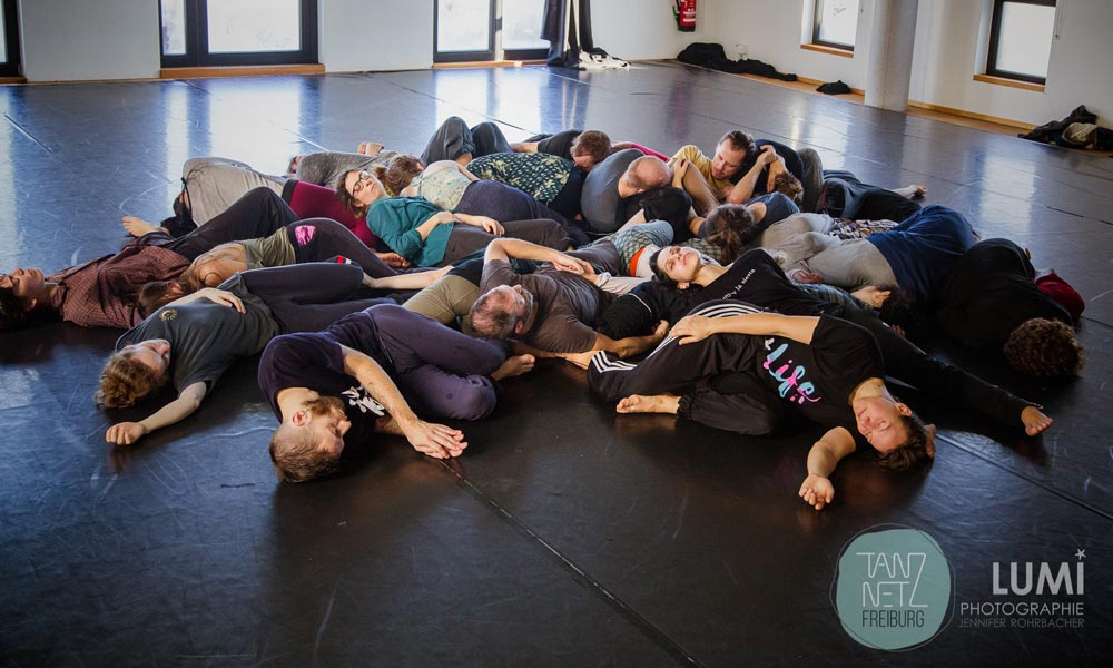 All the dancers together with Anna Kempin are laying on the floor during Tanznetz Freiburg dance workshop