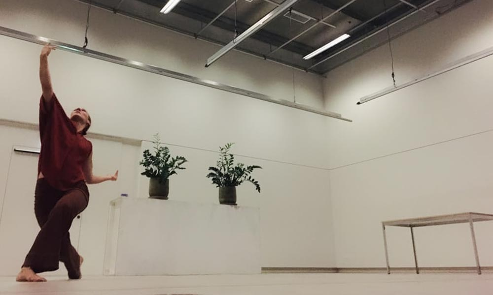 Anna Kempin captured performing at Atlas 2 contemporary dance project, standing and raising one hand high