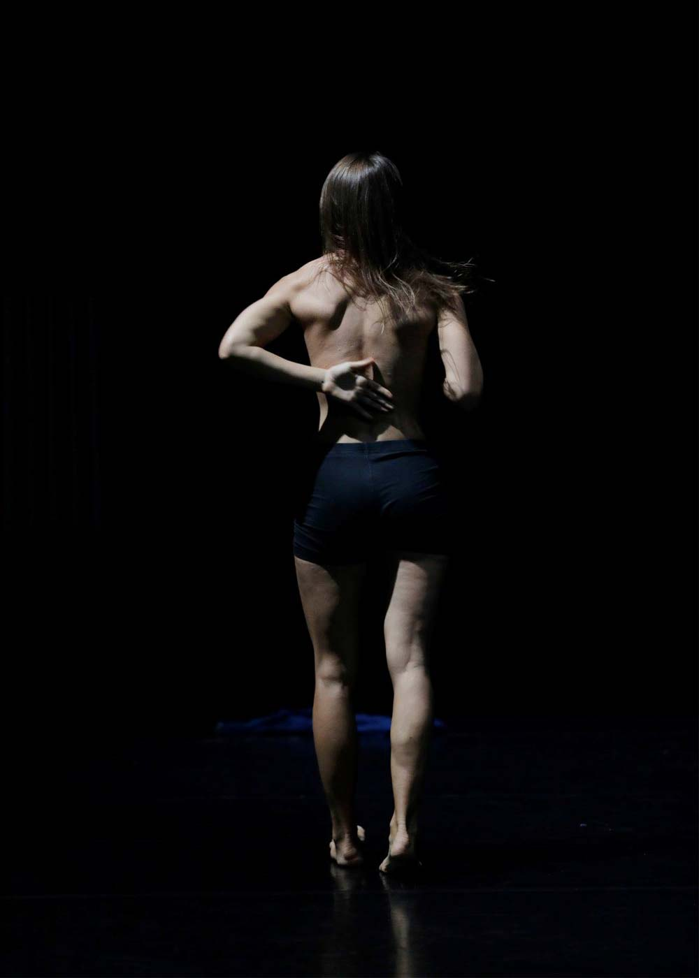Anna Kempin captured during her InBetWeEn A Shock dance performance, displaying her muscular back