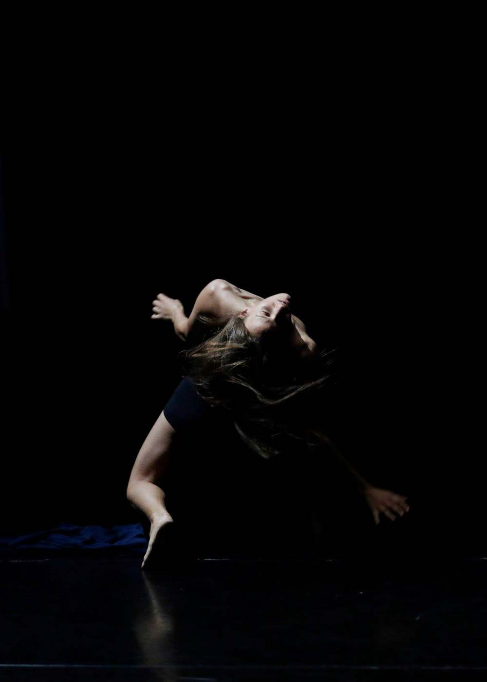 Anna Kempin is balancing on her toes with head raised towards the ceiling, during InBetWeEn A Shock dance performance