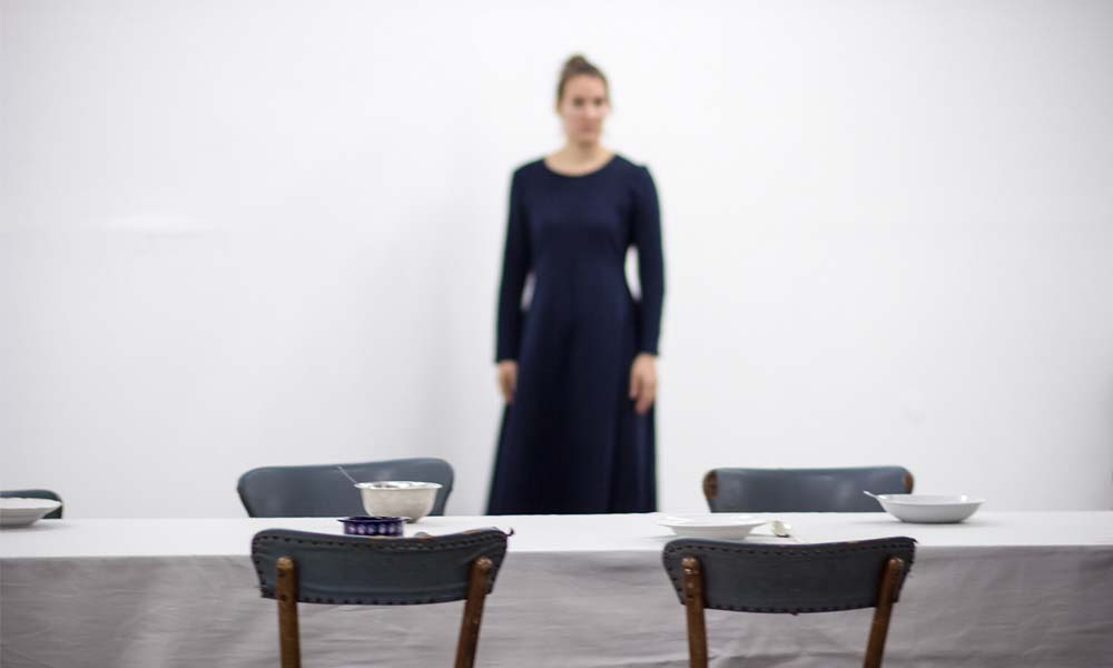 Anna Kempin captured performing VANITAS while standing behind a table with four chairs