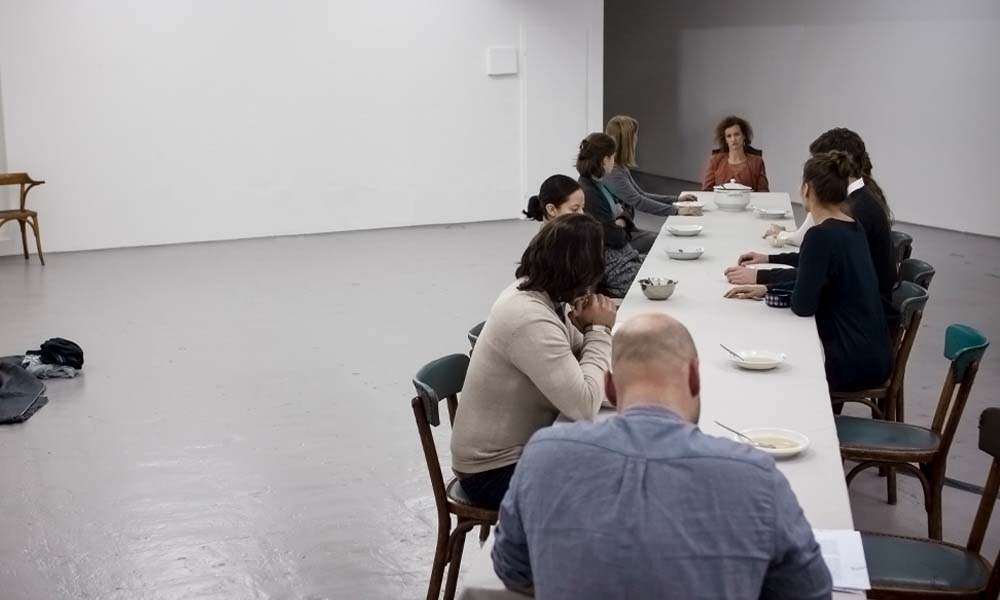 12 performers together with Anna Kempin in VANITAS sitting at the table and watching one viewer