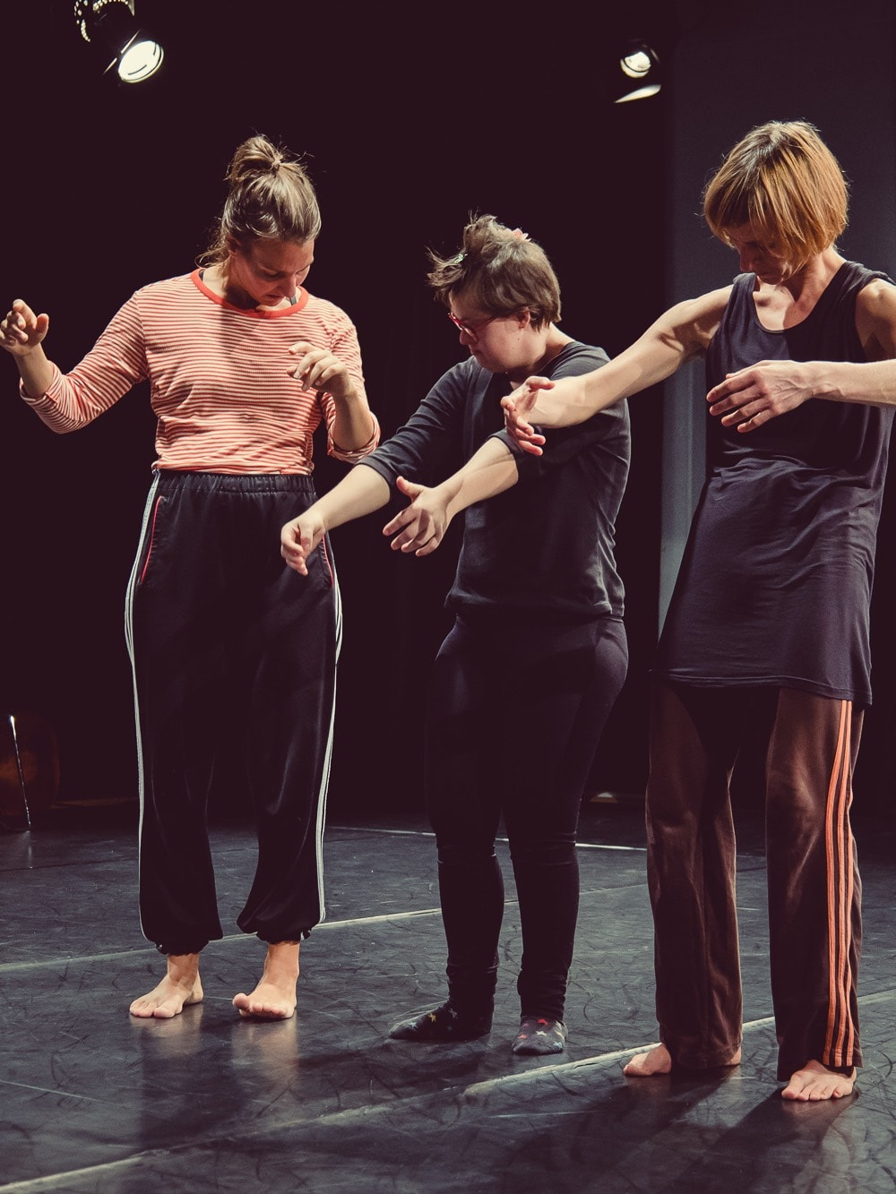 Dancer Anna Kempin, Christina Bischof and Rica Matthes dancing contemporary dance by standing and looking at their own bodies.