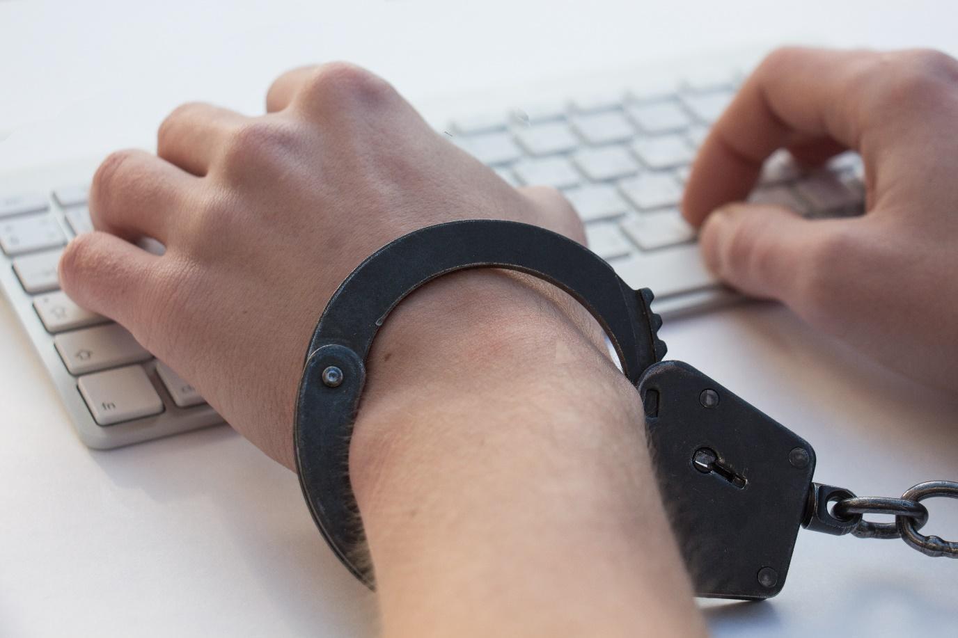 Hände in schwarzen Handschellen auf weißer Tastatur