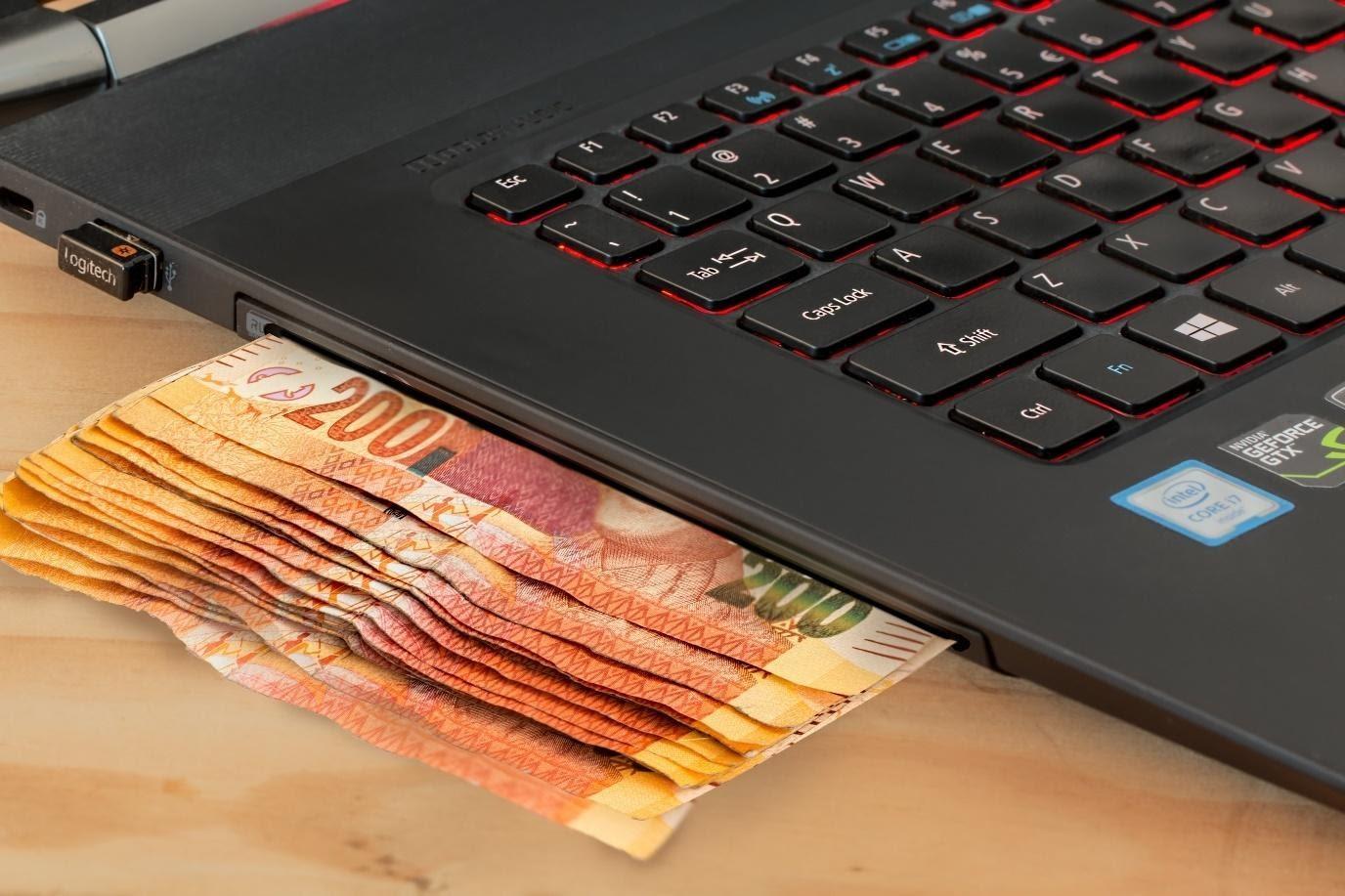 Geldscheine unter schwarzem Notebook