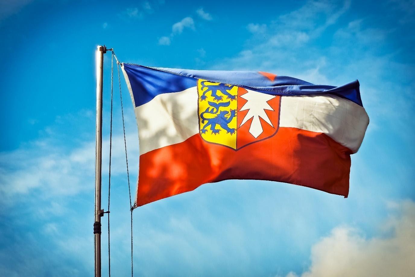 Flagge von Schleswig-Holstein vor blauem Himmel