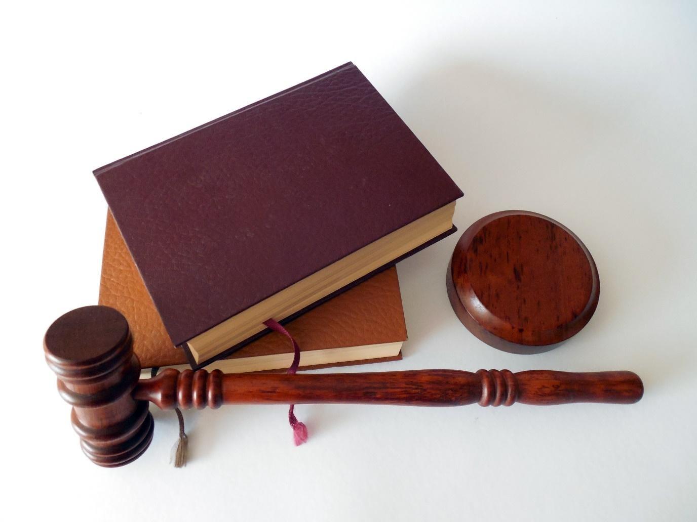 Richterhammer und zwei Gesetzbücher auf weißer Ebene