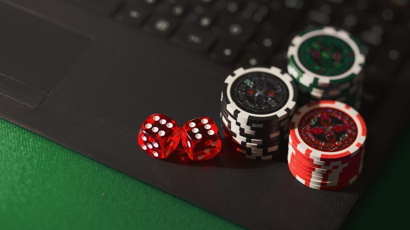 Pokerchips in Stapeln und rote Würfel auf Notebook